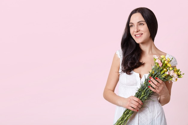 Young happy woman holding bouquet Free Photo