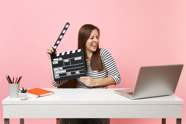 Young happy woman holding classic black film making clapperboard working on project while sit at office with laptop isolated on pastel pink background. achievement business career concept. copy space.