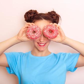 Молодая счастливая женщина, держащая пончики