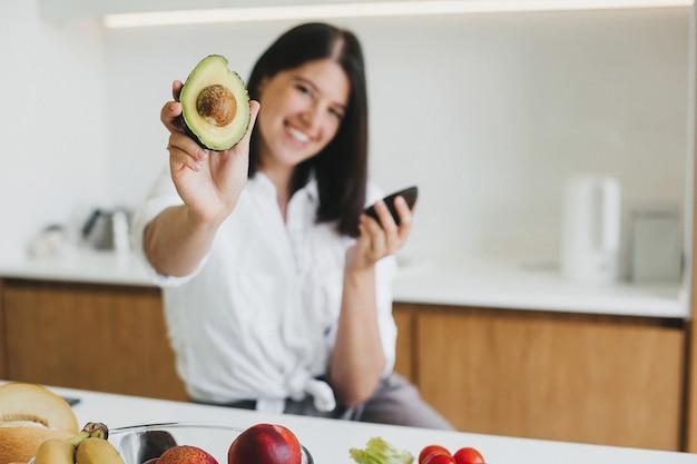 잘 익은 아보카도 반쪽을 손에 들고 신선한 과일과 야채가 있는 현대적인 흰색 주방에서 웃고 있는 젊은 행복한 여성. 건강한 식생활과 가정 요리 개념.