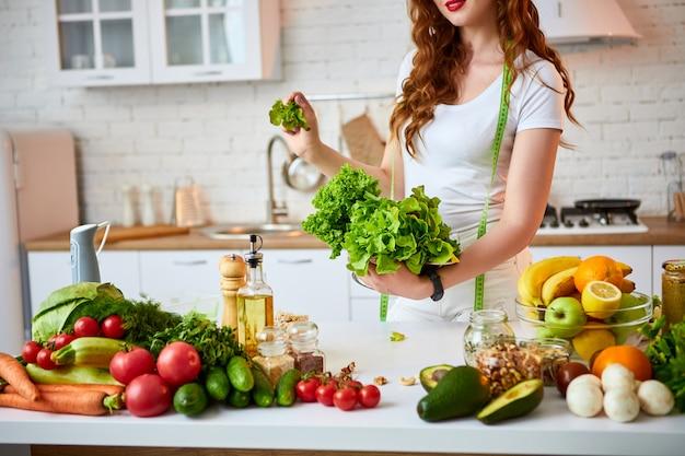 Молодая счастливая женщина держа салат выходит для делать салат в красивую кухню с зелеными свежими ингридиентами внутри помещения. здоровая пища и диета концепции. потеря веса