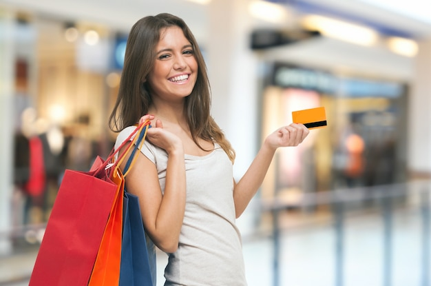 Young happy woman holding shopping bags and a credit card