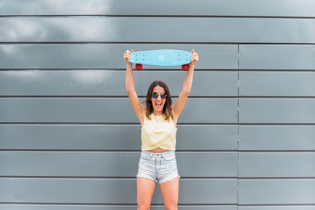 Young happy woman holding skateboard over head