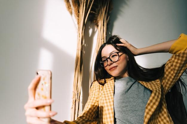 Молодая счастливая женщина, держащая смартфон, смотрящий на ячейку, с помощью мобильного телефона