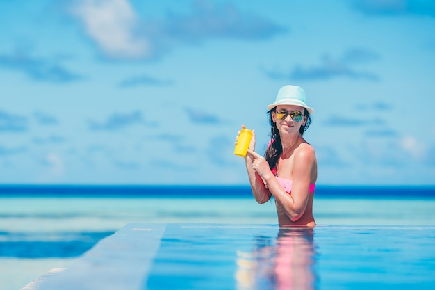 Young happy woman holding suntan lotion