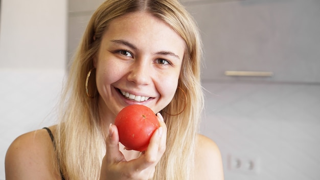 Young happy woman holding tomato and smiling on of modern white kitchen. healthy food concept. home cooking