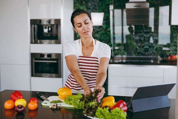 The young happy woman holding vegetables in hands in kitchen with laptop on the table