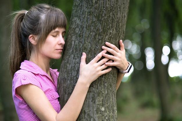 夏の公園で大きな木の幹を抱いて若い幸せな女