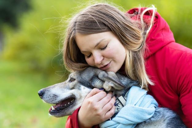 犬を抱き締める若い幸せな女性。ペットの養子縁組。女性の所有者とチェコスロバキア。