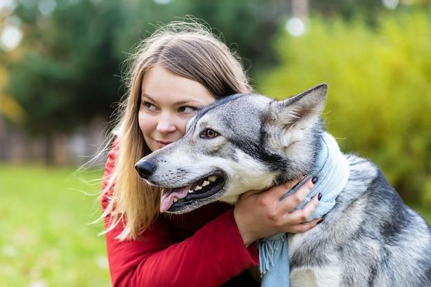 犬を抱き締める若い幸せな女性