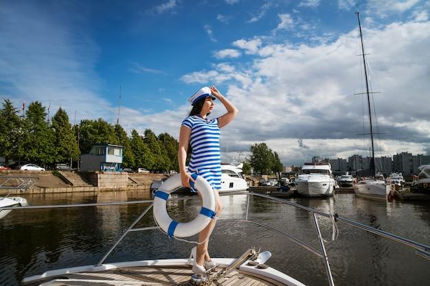 救命浮環を手にポーズをとってヨットの上に立っている青い縞模様のドレスを着た若い幸せな女性