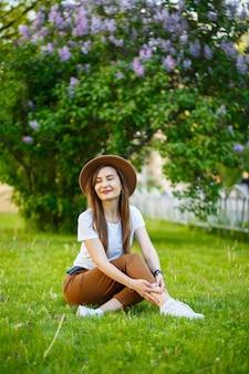 帽子をかぶった若い幸せな女性は、公園の緑の芝生に座っています。明るい晴れた夏の日に彼女の顔に笑顔でヨーロッパの外観の女の子