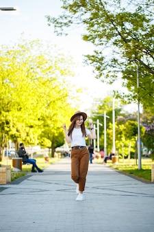 帽子をかぶった若い幸せな女性が公園の路地を歩いています。明るい晴れた夏の日に彼女の顔に笑顔でヨーロッパの外観の女の子