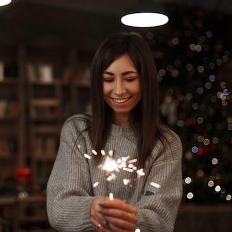 Молодая счастливая женщина в вязаном свитере держит в руке удивительный бенгальский огонь в винтажной комнате. веселого рождества и счастливого нового года. девушка улыбается.
