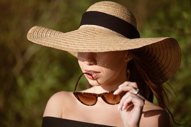 해변에서 화창한 여름 날에 포즈 선글라스 밀짚 모자 근접 촬영에 젊은 행복한 여자
