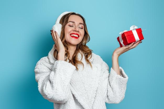 白いフェイクファーのコートを着た若い幸せな女性