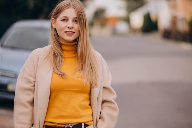 Молодая счастливая женщина в бежевом пальто