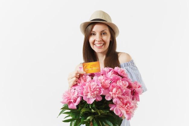 파란 드레스를 입은 젊은 행복한 여성, 신용 은행 카드, 돈, 흰색 배경에 격리된 아름다운 분홍색 모란 꽃다발을 들고 있는 모자. 비즈니스, 배달, 온라인 쇼핑 개념입니다. 공간을 복사합니다. 프리미엄 사진