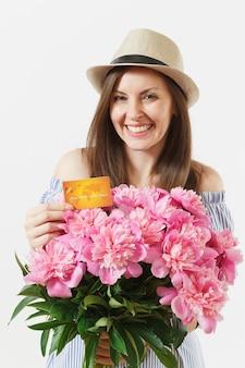 青いドレス、クレジット銀行カード、お金、白い背景で隔離の美しいピンクの牡丹の花の花束を保持している帽子の若い幸せな女性。ビジネス、配達、オンラインショッピングのコンセプト。スペースをコピーします。