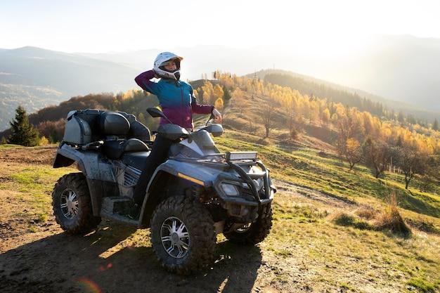 해질녘 가을 산에서 atv 쿼드 오토바이를 타고 극단을 즐기는 보호용 헬멧을 쓴 젊은 행복한 여성.