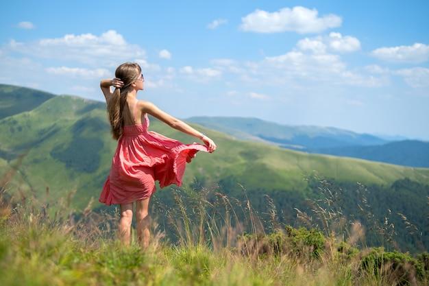 Молодая счастливая женщина в красном платье гуляет по траве поля в ветреный день в горах лета.