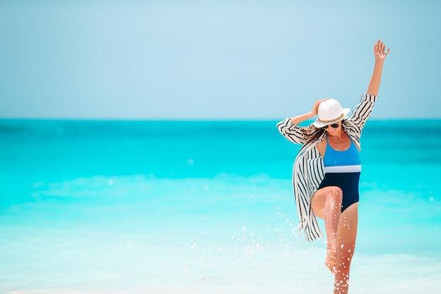 Молодая счастливая женщина в купальнике на белом пляже