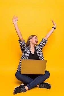 Молодая счастливая женщина в белой футболке сидит за ноутбуком и празднует победу и успех над желтой стеной