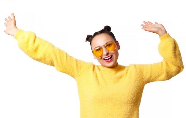 黄色いセーターと白で隔離されるガラスの若い幸せな女
