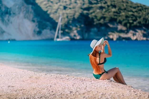 Молодая счастливая женщина сидит на красивом пляже