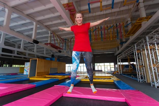 Молодая счастливая женщина прыгает на батуте в помещении.