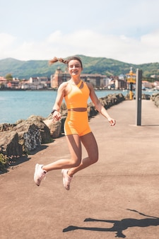 포트에서 설정 오렌지 스포츠와 함께 점프 젊은 행복 한 여자