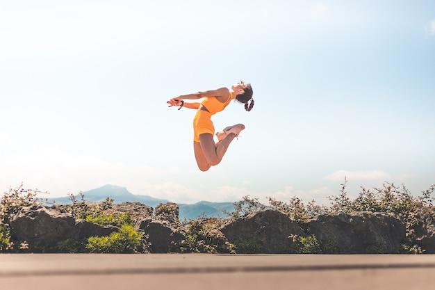 푸른 하늘 배경으로 설정 오렌지 스포츠와 점프 젊은 행복 한 여자