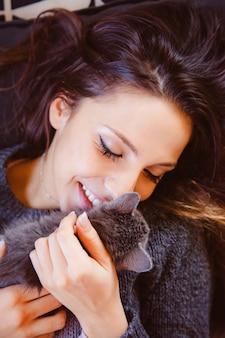 優しい愛で子猫にキス若い幸せな女。陽気な女性が猫を養子にしています。