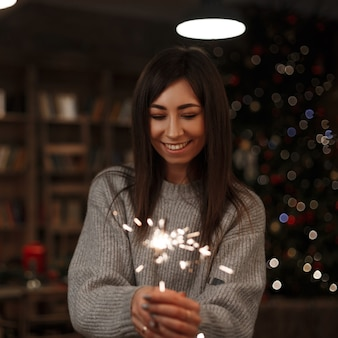 Young happy woman in a knitted sweater holds an amazing sparkler in her hand in a vintage room. merry christmas and happy new year. girl smiling.