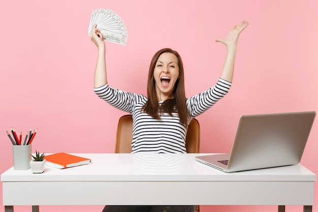 Young happy woman laughing screaming spreading hands holding bundle lots of dollars, cash money work at white desk with pc laptop