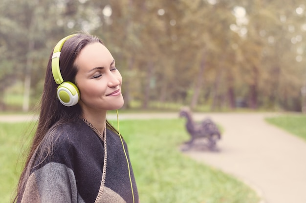 Young happy woman listening music from smartphone with headphones in a quiet park