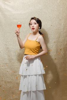 離れて目をそらし、孤立したシャンパンと笑顔の若い幸せな女性