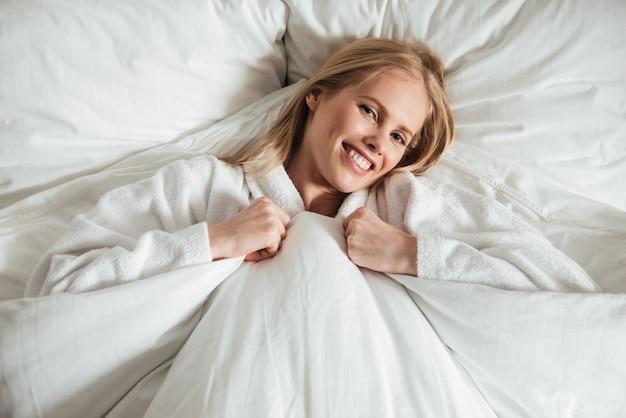 Молодая счастливая женщина лежа на большой белой кровати с одеялом