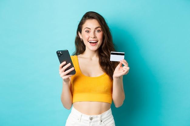 Giovane donna felice che fa ordini online, fa acquisti con carta di credito e smartphone, guarda stupita la telecamera, in piedi su sfondo blu.