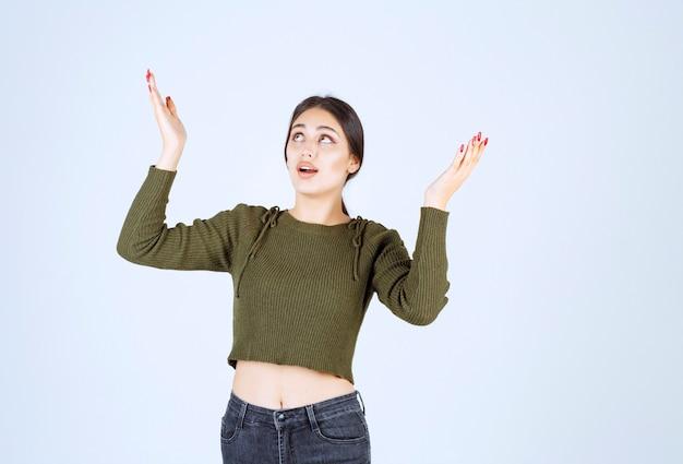 Молодая счастливая модель женщины стоя и поднимая руки.