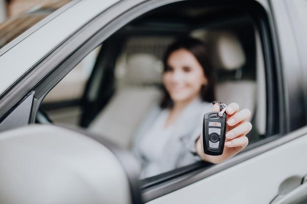 Giovane donna felice vicino alla macchina con le chiavi in mano. concetto di acquisto di auto. concentrati sulla chiave.