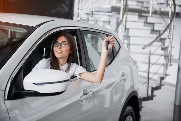 Young happy woman near the car with keys in hand