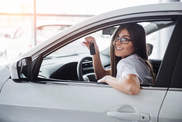 Молодая счастливая женщина возле автомобиля с ключами в руке