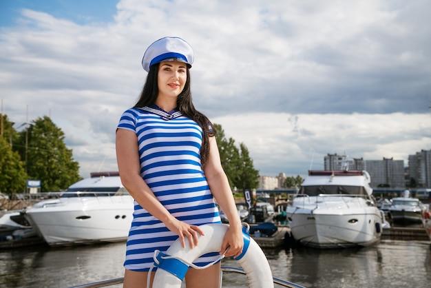 夏の晴れた日に雲と青い空の背景に救命浮環を手にポーズをとってヨットの上に立つ青い縞模様のドレスを着た白人の若い幸せな女性 Premium写真