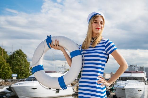 夏の晴れた日に雲と青い空の彼女の手で救命浮輪とポーズをとってヨットの上に立っている青い縞模様のドレスで白人の外観の若い幸せな女性