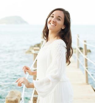 바다, 여름 시간 근처 다리에 젊은 행복 한 여자