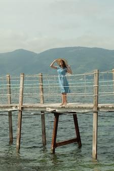 海の近くの橋の上の若い幸せな女性