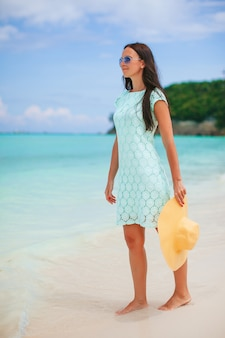 白いビーチを歩いて若い幸せな女性。熱帯の海岸の若い美しい女性。