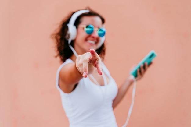 屋外のヘッドセットと携帯電話で音楽を聴く若い幸せな女。人差し指でカメラを指しています。街のライフスタイル。夏時間。クローズアップビュー