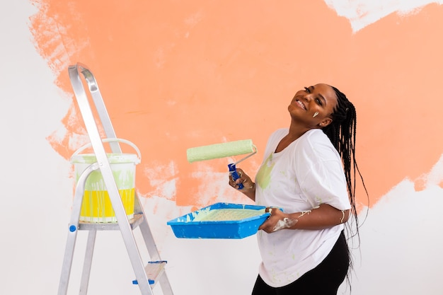 Young happy woman painting interior wall with paint roller in new house.